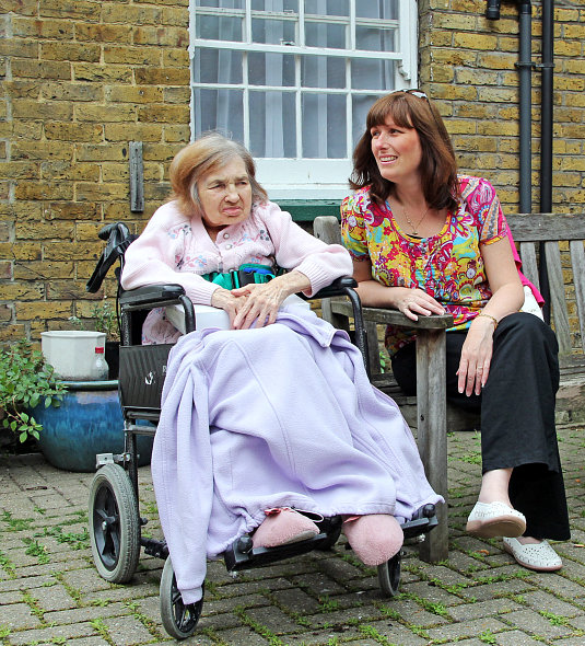 elderly woman in wheelchair with her caretaker